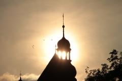 Kościół Pw. Św Jakuba w otoczeniu gołębi i z słońcem w tle